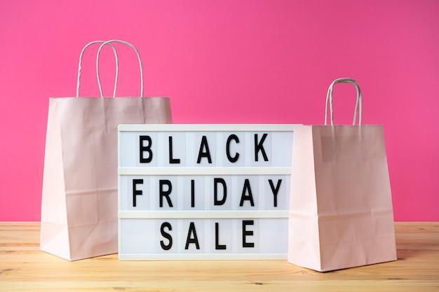 Schwarzer freitag-schriftzug auf leuchtkasten mit öko-einkaufstüten aus papier. auf einem hellen farbigen hintergrund.
