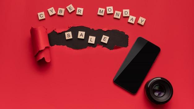 Schwarzer freitag und cyber montag, modernes smartphone und objektiv für die kamera auf rot und schwarz.