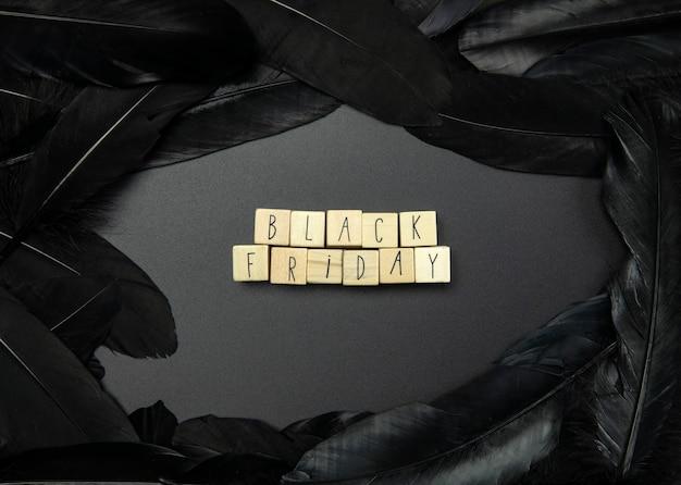 Schwarzer freitag und verkauf auf schwarzem hintergrund, umgeben von draufsicht mit dunklen federn, geschäftskonzept