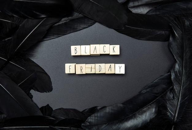 Schwarzer freitag und verkauf auf schwarzem hintergrund, umgeben von draufsicht mit dunklen federn, modernes design des geschäftskonzepts