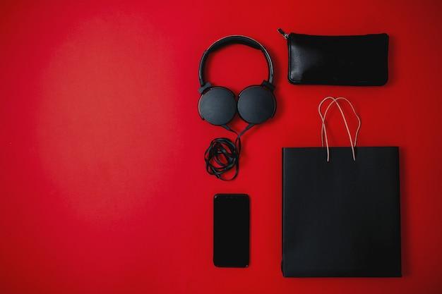 Schwarzer freitag verkauf flach legen, schwarzer freitag tasche, kopfhörer, handy, tasche und brieftasche auf der roten oberfläche,