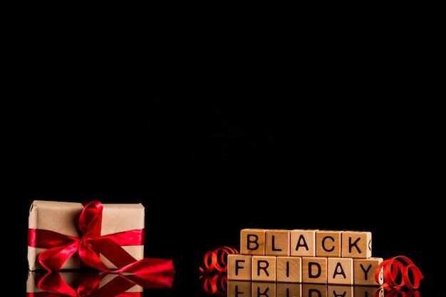 Schwarzer freitag-würfel mit geschenk auf schwarzem hintergrund