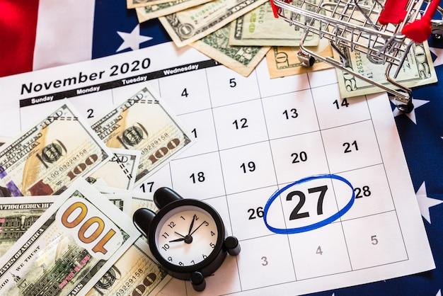 Schwarzer freitaghintergrund mit einkaufswagen und wecker mit tag am 27. november 2020 und amerikanischer flagge.
