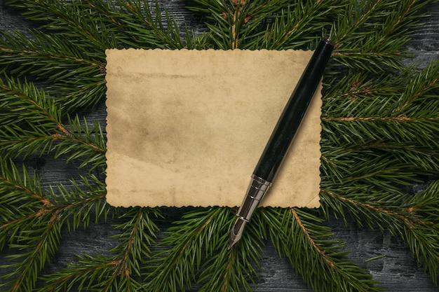 Schwarzer füllfederhalter auf einem alten stück papier gegen die oberfläche der fichtenzweige