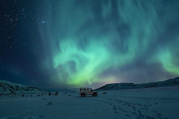 Schwarzer geländewagen auf schneebedecktem feld unter grünen auroralichtern
