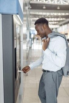 Schwarzer geschäftsmann an kaffeemaschine im autohaus. erfolgreiche geschäftsperson auf der automobilausstellung, schwarzer mann in der abendgarderobe