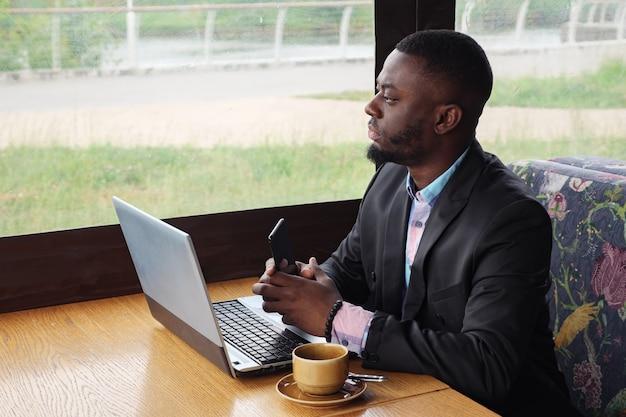 Schwarzer geschäftsmann arbeitet am laptop mit smartphone im café und trinkt kaffee