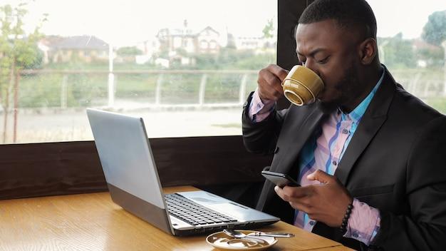 Schwarzer geschäftsmann arbeitet am laptop mit smartphone im café und trinkt kaffee.