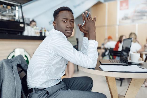 Schwarzer geschäftsmann, der am laptop im autohaus sitzt. erfolgreiche geschäftsperson auf der automobilausstellung, schwarzer mann in der abendgarderobe, automobilausstellungsraum