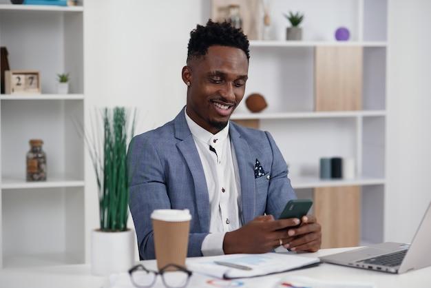 Schwarzer geschäftsmann, der auf den internetseiten auf dem smartphone surft und eine pause bei der arbeit im modernen büro hat.