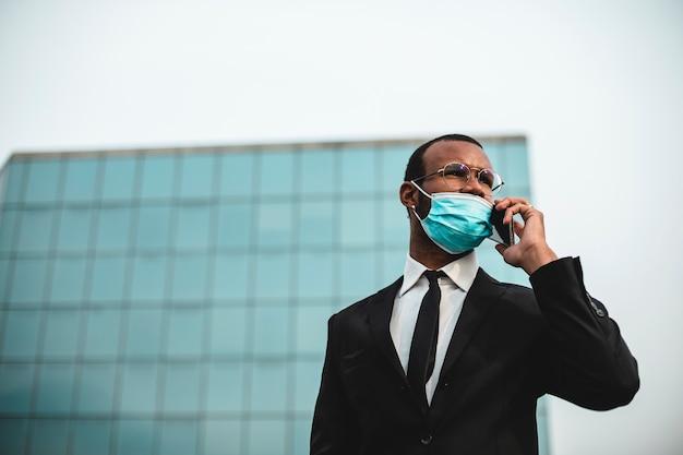 Schwarzer geschäftsmann, der eine viruskronenschutzmaske mit seinem handy trägt.