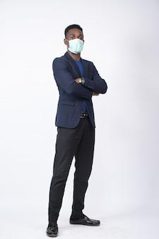 Schwarzer geschäftsmann, der einen anzug und eine gesichtsmaske trägt und mit verschränkten armen steht - das neue normale konzept