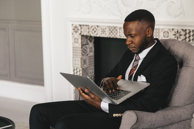 Schwarzer geschäftsmann, der laptop für die analyse der datenbörse verwendet
