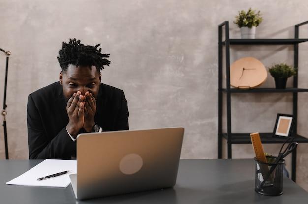 Schwarzer geschäftsmann, der laptop zur analyse von datenbörsen, devisenhandelsdiagrammen, börsenhandel online verwendet using