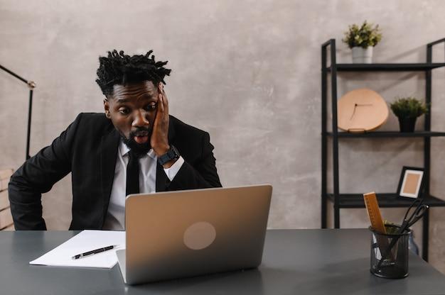 Schwarzer geschäftsmann, der laptop zur analyse von datenbörsen, devisenhandelsdiagrammen, online-börsenhandel, reaktion auf fallende aktien verwendet.