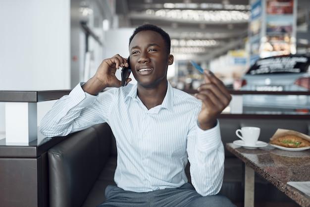 Schwarzer geschäftsmann, der per telefon, autoausstellungsraum spricht. erfolgreiche geschäftsperson auf der automobilausstellung, schwarzer mann in der abendgarderobe