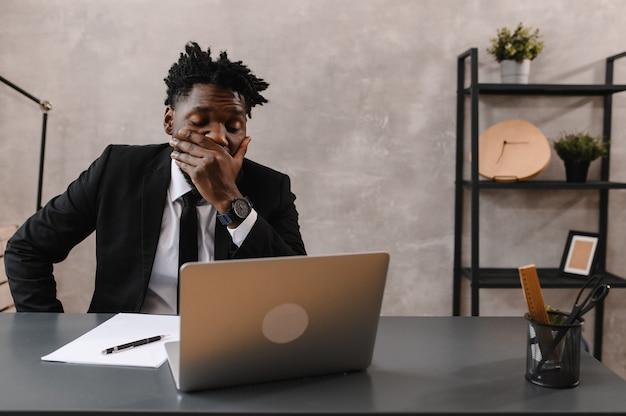 Schwarzer geschäftsmann mit laptop für die analyse von datenbörsen using
