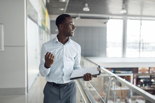 Schwarzer geschäftsmann mit notizbuch im einkaufszentrum food-court. erfolgreicher geschäftsmann, schwarzer mann in formeller kleidung, einkaufszentrum