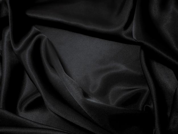 Schwarzer gewebebeschaffenheitshintergrund, glatte schwarze farbe des gewellten gewebes, luxuxsatinstofftext