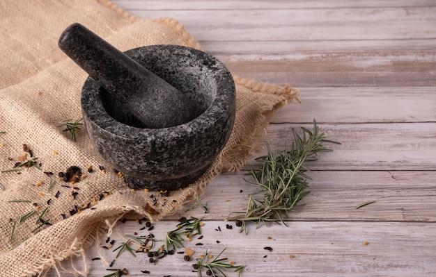 Schwarzer granitmörser auf beigem küchentuch und holzuntergrund