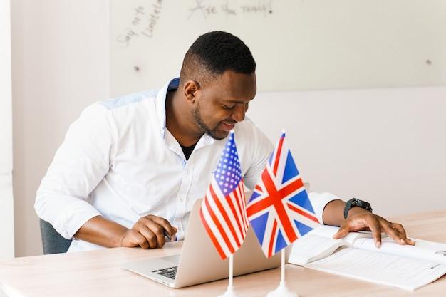 Schwarzer gutaussehender mann benutzt seinen laptop für online-arbeit entsprechend sozialer distanzierung