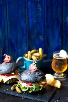 Schwarzer hamburger mit rindfleisch, salat und pommes frites. frisches bier in einem glas. trends bei streetfood. ein kalorienessen. kopieren sie platz