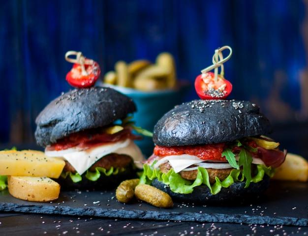 Schwarzer hamburger mit rindfleisch, salat und pommes frites. trends bei streetfood. ein kalorienessen. fast food. kopieren sie platz