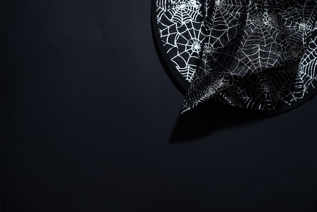 Schwarzer hexenhut mit einem muster von spinnennetzen auf schwarzem hintergrund