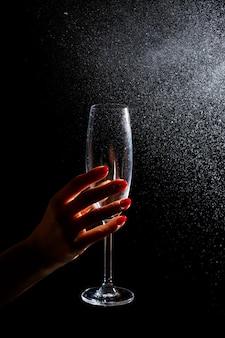 Schwarzer hintergrund darauf ist eine nahaufnahme eines sauberen glases in seiner hand. auf ein glas wasser sprühen. isolierglas