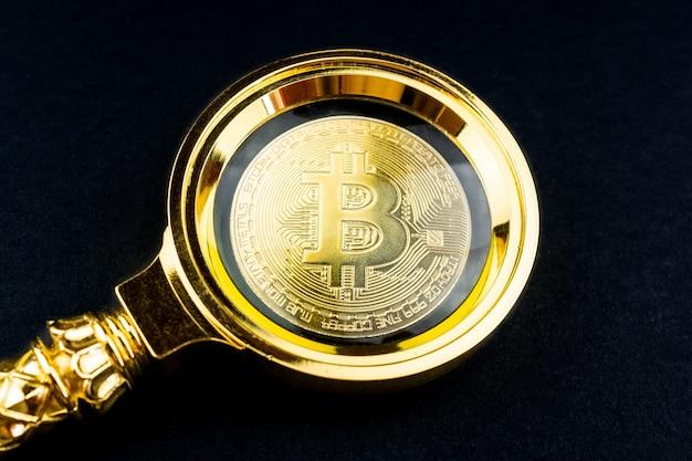 Schwarzer hintergrund des bitcoin und des vergrößerungsglases