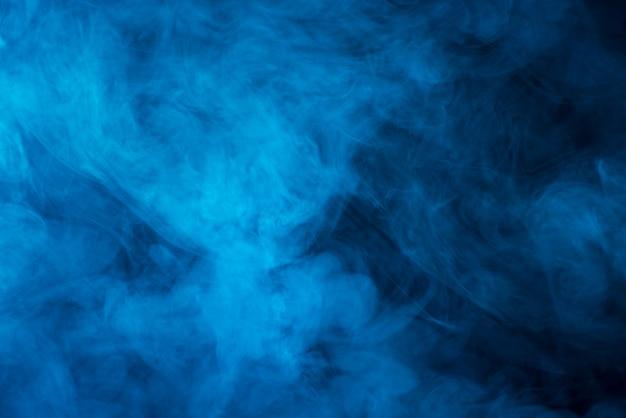 Schwarzer hintergrund des blauen dampfes