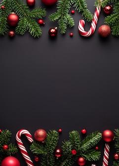 Schwarzer hintergrund für weihnachten und neujahr. dekorative bordüre aus tannenzweigen, weihnachtskugeln und zuckerstangen