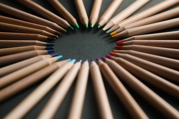 Schwarzer hintergrund mit buntstiften. abgerundeter rahmen
