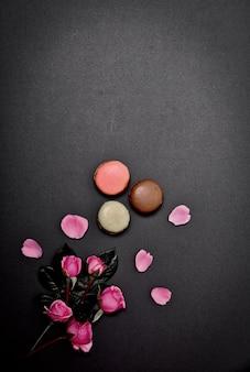 Schwarzer hintergrund mit makronen und einem blumenstrauß von rosa rosen