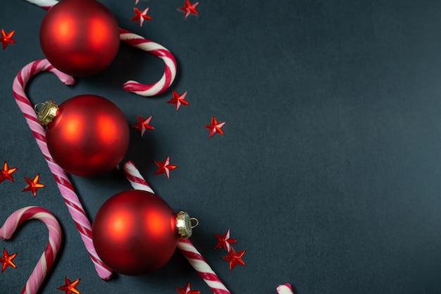 Schwarzer hintergrund mit roten weihnachtsbällen, zuckerstangen und sternen. overhead-wohnung lag mit textfreiraum