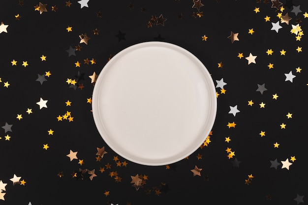Schwarzer hintergrund mit sternen, die mit leerem plattenmodell leuchten frohes neues jahr hintergrundkopierraum