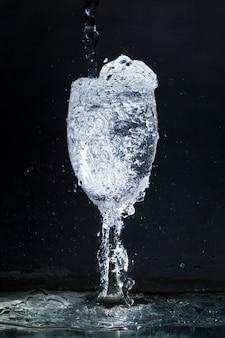 Schwarzer hintergrund mit überfließendem glas wasser