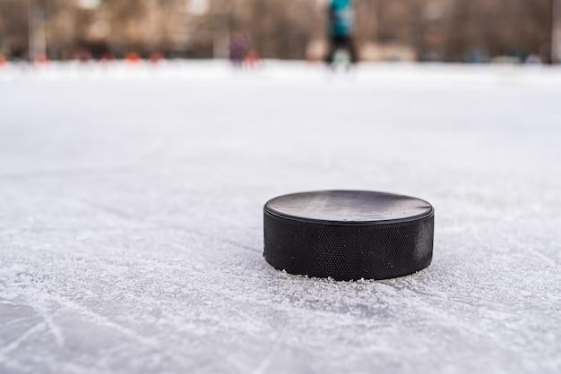 Schwarzer hockey-puck liegt auf eis im stadion