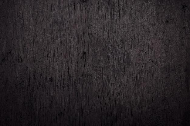 Schwarzer hölzerner hintergrund mit kratzern und staub. detail der verkratzten holzoberfläche.