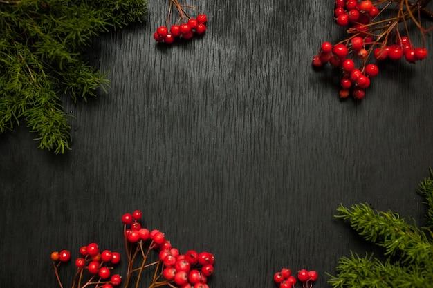 Schwarzer hölzerner hintergrund mit moos und eberesche an den seiten. grunge textur