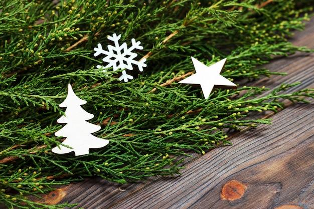 Schwarzer hölzerner weihnachtshintergrund. zweige der thuja. ursprüngliches, frisches blumen für weihnachtskarte. leeren raum für urlaubsgrüße
