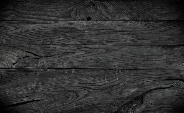 Schwarzer holzhintergrund verkohlte bretter bemalte schwarze fleckbretter