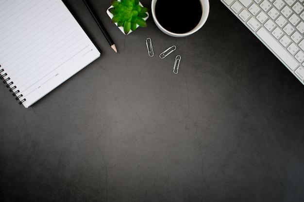 Schwarzer holztisch mit smartphone, notizbuch, kaffee, blättern und zubehör arbeiten, social media. ansicht von oben. flach liegen.