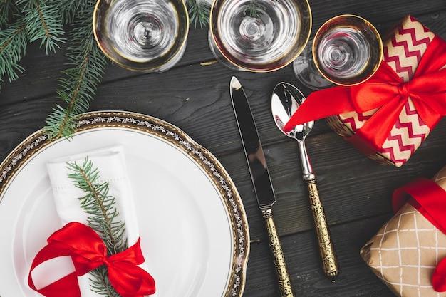 Schwarzer holztisch mit stilvollem weihnachtsgedeck