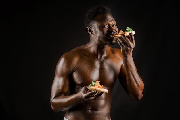 Schwarzer hübscher nackter mann isst eine pizza