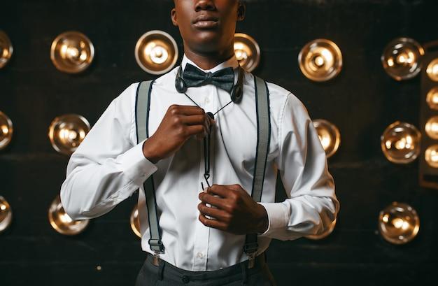 Schwarzer jazz-performer auf der bühne mit scheinwerfern. schwarzer jazzer, der in der szene vorführt