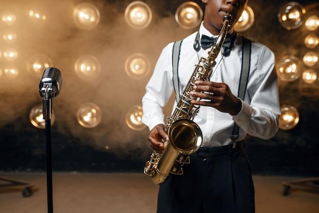 Schwarzer jazz-performer spielt saxophon auf der bühne mit scheinwerfern. schwarzer jazzer, der in der szene vorführt