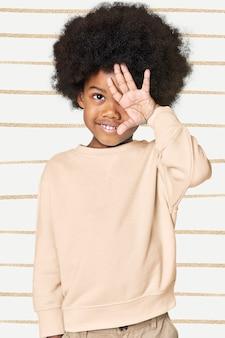 Schwarzer junge, der cremefarbenen pullover trägt