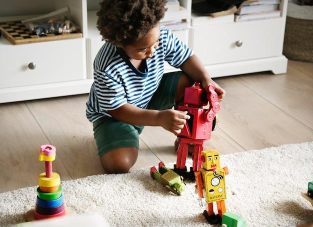 Schwarzer junge, der zu hause roboter spielt