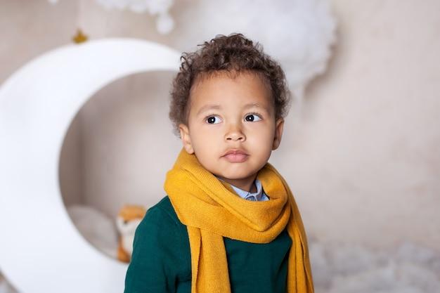 Schwarzer junge hautnah. porträt eines fröhlich lächelnden schwarzen jungen in einem gelben schal. porträt eines kleinen afroamerikaners. schwarzer. nachdenkliches kind. kindheit. kind spielt im kindergarten. gesicht eines kleinen jungen